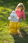 Toddler playing with little man fire hydrant.