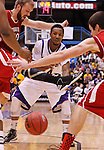 SIOUX FALLS, SD - MARCH 9:  Remy Roberts-Burnett #24 of Western Illinois passes through University of South Dakota defenders during their men's quarter-final game at the 2013 Summit League Basketball Championships Saturday at the Sioux Falls Arena.  (Photo by Dick Carlson/Inertia)