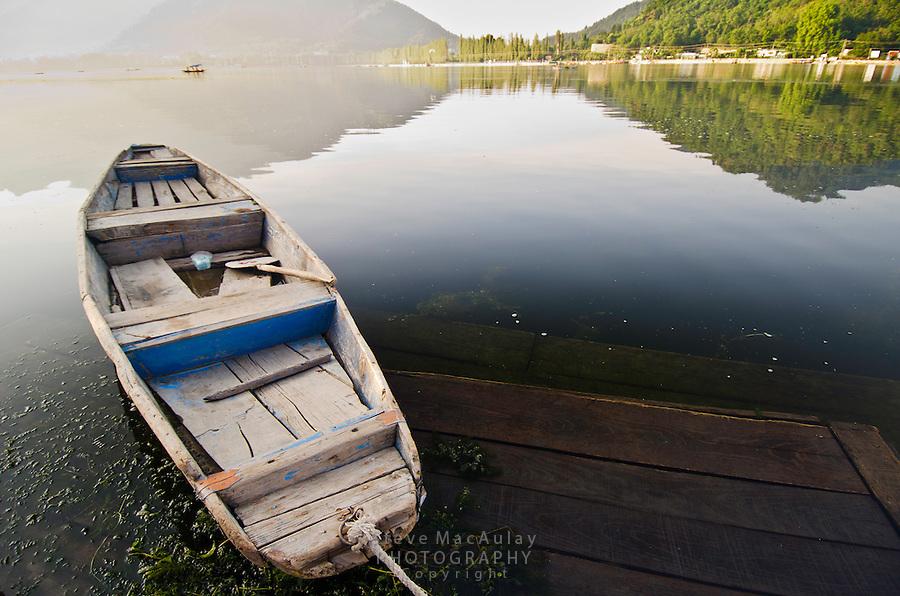 "Traditional ""shikara"" row boat at sunrise on the shore of Dal Lake, Srinagar, Kashmir, India."