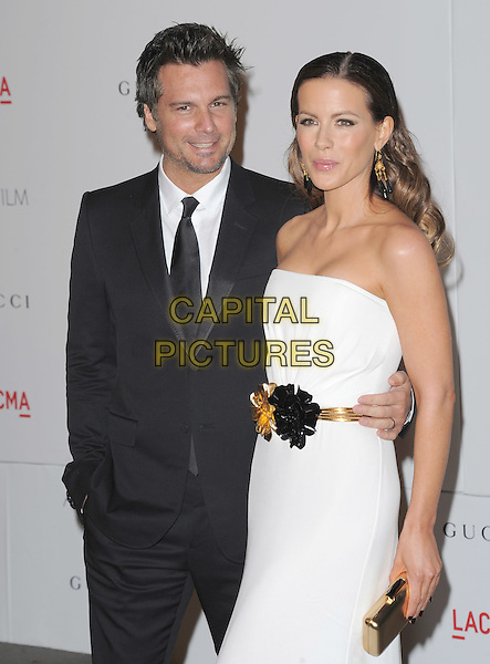 Len Wiseman & Kate Beckinsale.The Inaugural Art and Film Gala held at LACMA in Los Angeles, California, USA..November 5th, 2011   .half length dress white strapless dress gold black belt corsage clutch bag suit married husband wife  arm around waist .CAP/RKE/DVS.©DVS/RockinExposures/Capital Pictures.