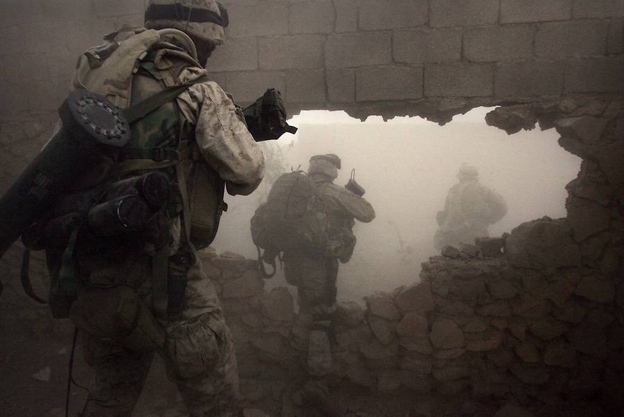 US Marines and Iraqi soldiers with Golf Co. 2nd Battalion 1st Marines make their way through a breach in a wall made by combat engineers to avoid walking through open streets and exposing themselves to sniper fire or opening gateways and doors which could be booby-trapped or conceal waiting insurgents during the third day of Operation Steel Curtain, an operation to clear Husaybah (a city on the Iraq-Syrian border) of insurgents on Tues. Nov. 8, 2005.