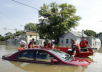Members of the United States Coast Guard check an abandoned car as flood waters of the Blanchard River start to recede after heavy rains caused flooding Thursday, August 23, 2007, in Findlay, Ohio. The Blanchard River was close to 7 feet above flood stage at Findlay yesterday morning, the highest since a 1913 flood.