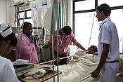 A doctor and a team of nurses with the father of the patients prays for the patient as he lays in the intensive care unit of the Duncan Hospital in Raxaul, Bihar, India.