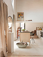 The simple kitchen, in what was once the stables, has a contemporary polished concrete floor. Shelving and appliances are built into a concrete unit and a zinc-topped laboratory table stands in the centre