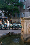 Village fountain, Village square; French sidewalk cafes, Saint Florent; Corsica, France, Mediterranean Coast, Coastal towns in Corsica,