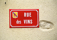 A red street sign saying rue des Vins, the street of the wines, on a stone wall, with an emblem showing Saint Martin, a patron saint of wine, Languedoc, Languedoc-Roussillon, France