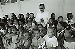 Reverend Johannes Sturman, of the Emmanuel Congregational church sing with children of a school choir at the Olyfenshoutsdrift primary school on February 8, 2002 in Loisevale, Upington, South Africa Loisevale, a poor and destitute colored/black township where unemployment is high, and many social problems including domestic violence and alcohol abuse. Her father raped baby Thsepang, an 8-month old baby here in October 2001. The baby rape shocked the country. (Photo: Per-Anders Pettersson)