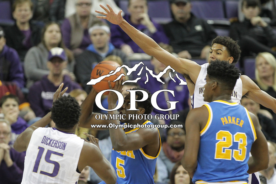 JAN 1, 2016:  Washington's #0 Marquese Criss tries to block the shot under the basket of UCLA's #5 Prince Ali.  Washington defeated #25 ranked UCLA 96-93 in double overtime at Alaska Airlines Arena in Seattle, WA.