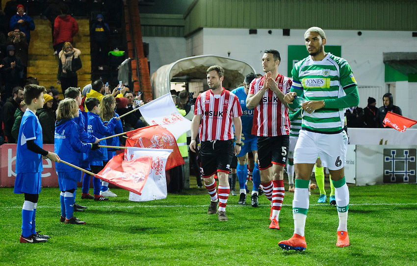 A fan on his stag do walks out as mascot prior to the game alongside Lincoln City's Jason Shackell after being set up by his friends<br /> <br /> Photographer Chris Vaughan/CameraSport<br /> <br /> The EFL Sky Bet League Two - Lincoln City v Yeovil Town - Friday 8th March 2019 - Sincil Bank - Lincoln<br /> <br /> World Copyright © 2019 CameraSport. All rights reserved. 43 Linden Ave. Countesthorpe. Leicester. England. LE8 5PG - Tel: +44 (0) 116 277 4147 - admin@camerasport.com - www.camerasport.com