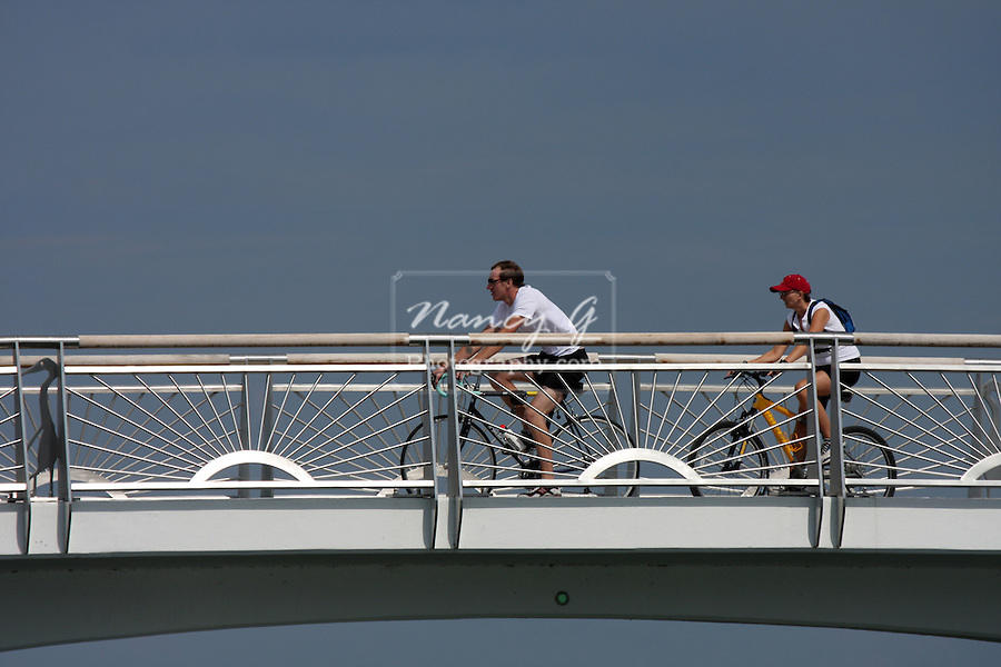 Two bikers riding over a bridge over the bay at the lake front.  Milwaukee and Lake Michigan