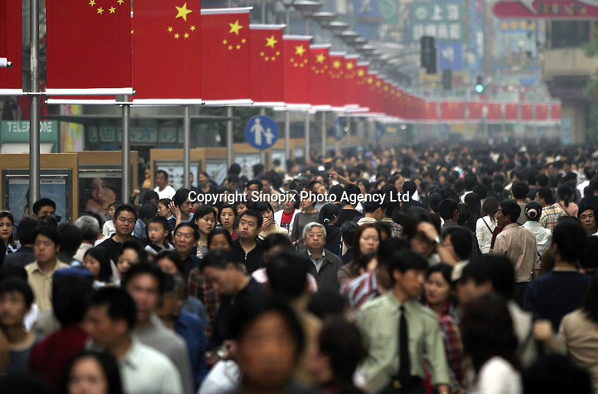 Crowds line the center shopping district of Nanjing Road on May Holiday Weekend in Shanghai, China. The long holiday surrounding May 1st offers a golden opportunity for tourism all around China..02-MAY-04