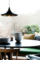 A contemporary pendant light hangs above a kitchen table. Cushions by Oyuna sit on the green bench seat.