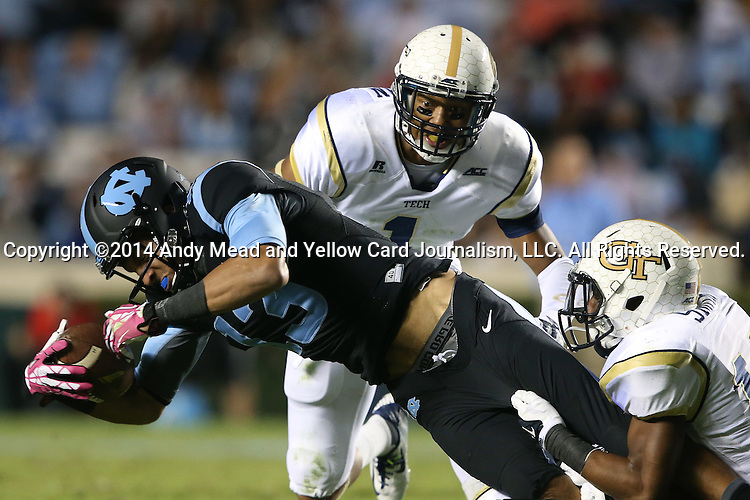 18 October 2014: UNC's Mack Hollins (13) is tackled by Georgia Tech's Demond Smith (right) and Isaiah Johnson (1). The University of North Carolina Tar Heels hosted the Georgia Tech Yellow Jackets at Kenan Memorial Stadium in Chapel Hill, North Carolina in a 2014 NCAA Division I College Football game. UNC won the game 48-43.
