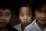 A little girl sticks her tongue out at the camera in rural Laos, near Luang Prabang.