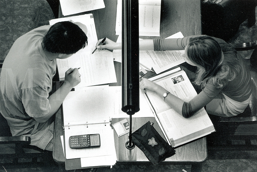 Overhead view of male and female college students studying at table.