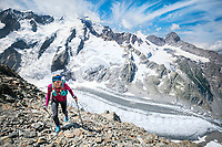 A trail runner in rocky terrain and above glaciers while climbing the Strahlegghorn, from Grindelwald, Switzerland