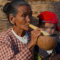 Woman smoking a cheerot (traditional cigar) at Minnanthu Village near Bagan, Myanmar/Burma