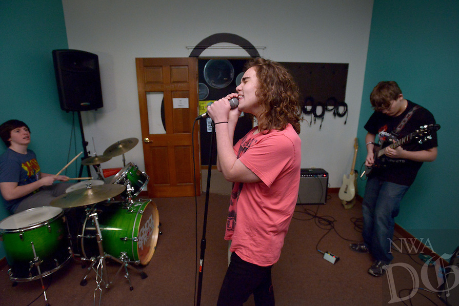 STAFF PHOTO BEN GOFF  @NWABenGoff -- 12/27/14 Carson Little, 15, from left, of Bentonville, Bryce Holcomb, 16, of Rogers and Jackson Muller, 16, of Rogers play classic rock songs as the dean's list advanced group rehearses at the School of Rock in Rogers on Saturday Dec. 27, 2014. The students are preparing for their next public performance, which will be during Last Night Fayetteville on December 31.