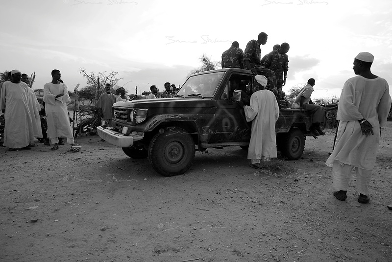 Borzaid, North Darfur, August 23, 2004.An 'Arab' village near Kutum. A group of janjaweed militiamen, commanded by Hafiz, a young man from Mastariha, came to distribute new Khaki uniforms to the village men under the supervision of a Sudanese Police officer.