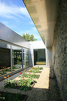 The metal structure of the house incorporates long windows made of sliding glass panels