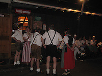 Germans in traditional clothing take a break outside a beer hall