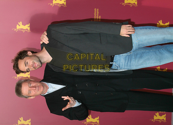"REGIS WARGNIER & JOSEPH FIENNES .February 10th, 2005.55th Berlin International Film Festival.Photocall for ""Man To Man"".half length arm over shoulder hand gesture.www.capitalpictures.com.sales@capitalpictures.com.©Capital Pictures"