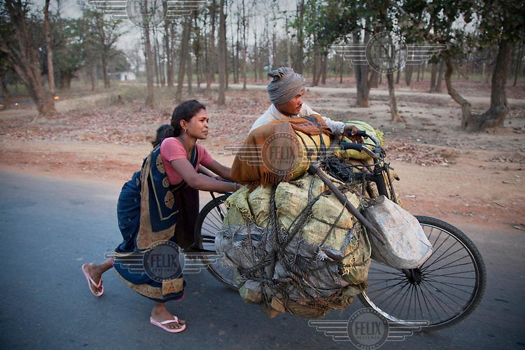 A man and his wife push their bicycle loaded with coal in a two-day trek to the market. The work pays about 500 rupees (GBP 7.40) which is shared with their underground digging team and others. They must also pay bribes to local police to enable them to continue what is officially an illegal activity..