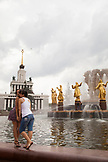 RUSSIA, Moscow. Visitors posing for a photo in front of the Peoples Friendship Fountain at the All-Russia Exhibition Center.