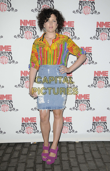 Annie Mac.attended the NME Awards 2012, O2 Academy Brixton, Stockwell Rd., London, England.February 29th, 2012.full length jean denim skirt pink purple sandals shoes clutch bag white orange green print shirt hand on hip  .CAP/CAN.©Can Nguyen/Capital Pictures.