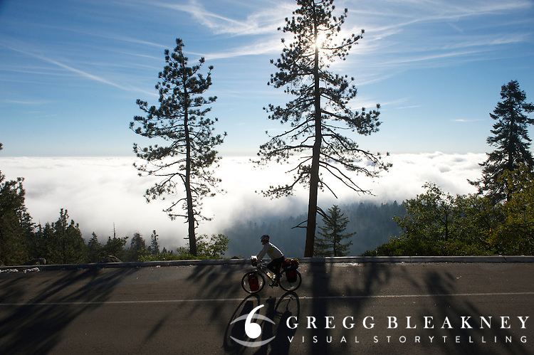 A touring cyclist spins above the clouds on Generals HWY @ 7,000 feet in Sequoia National Park - Adventure Cycling Sierra Cascades Route - Canada to Mexico Cycling Expedition