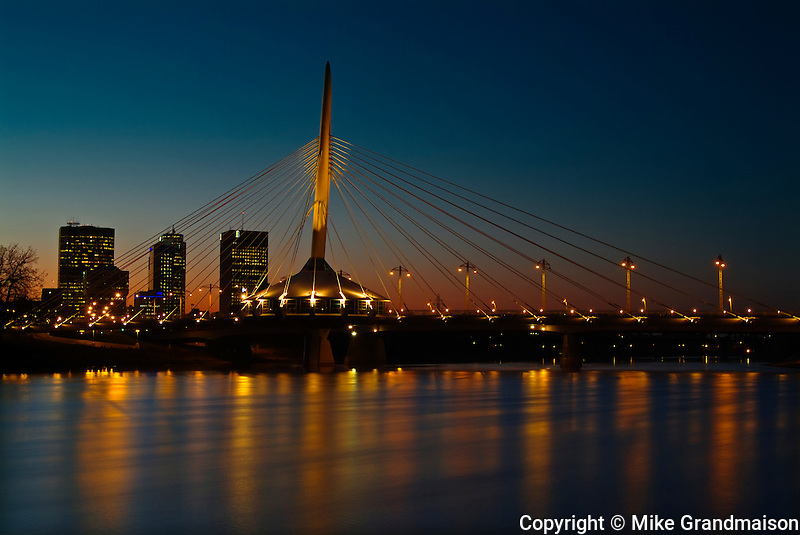 Esplanade Riel bridge and city skyline reflected in teh Red River at dusk<br /> Winnipeg<br /> Manitoba<br /> Canada