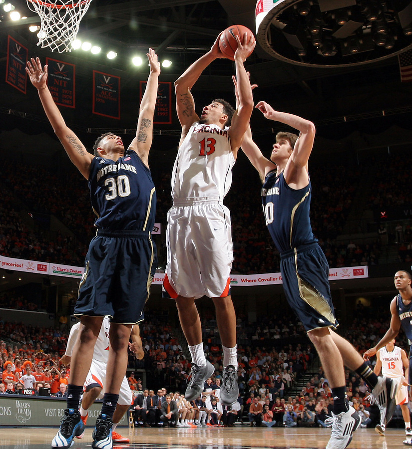 Virginia forward Anthony Gill (13) shoots between Notre Dame forward Zach Auguste (30) and Notre Dame forward Austin Burgett (20) during the game Saturday, February 22, 2014,  in Charlottesville, VA. Virginia won 70-49.