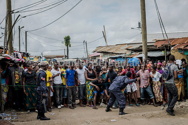 MONROVIA, LIBERIA - AUGUST 23, 2014:   A Liberian Police man strikes towards the front of a cordon quarantining the West Point neighbourhood, as residents wait for relatives to bring them food from outside of the quarantined area, during the fourth day of the government's Ebola quarantine on their neighbourhood on August 23, 2014 in Monrovia, Liberia.  Liberia's government announced Friday night that it would lift an Ebola quarantine on a large slum here in the capital, 10 days after attempts to cordon off the neighborhood from the rest of the city sparked deadly clashes and fueled doubts about President Ellen Johnson Sirleaf's ability to handle the outbreak.<br /> photo by Daniel Berehulak/Reportage by Getty Images