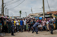 MONROVIA, LIBERIA - AUGUST 23, 2014:   A Liberian Police man strikes towards the front of a cordon quarantining the West Point neighbourhood, as residents wait for relatives to bring them food from outside of the quarantined area, during the fourth day of the government's Ebola quarantine on their neighbourhood on August 23, 2014 in Monrovia, Liberia.  Liberia&rsquo;s government announced Friday night that it would lift an Ebola quarantine on a large slum here in the capital, 10 days after attempts to cordon off the neighborhood from the rest of the city sparked deadly clashes and fueled doubts about President Ellen Johnson Sirleaf&rsquo;s ability to handle the outbreak.<br /> photo by Daniel Berehulak/Reportage by Getty Images