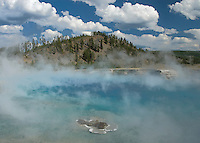 Firehole Lake steams while clouds of a cooler vapor float overhead, Yellowstone National Park