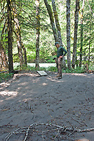 Volunteer photographer surveys sign buried by feet of flooded sand and silt at Grove of the Patriarchs, Mount Rainier National Park, Washington State