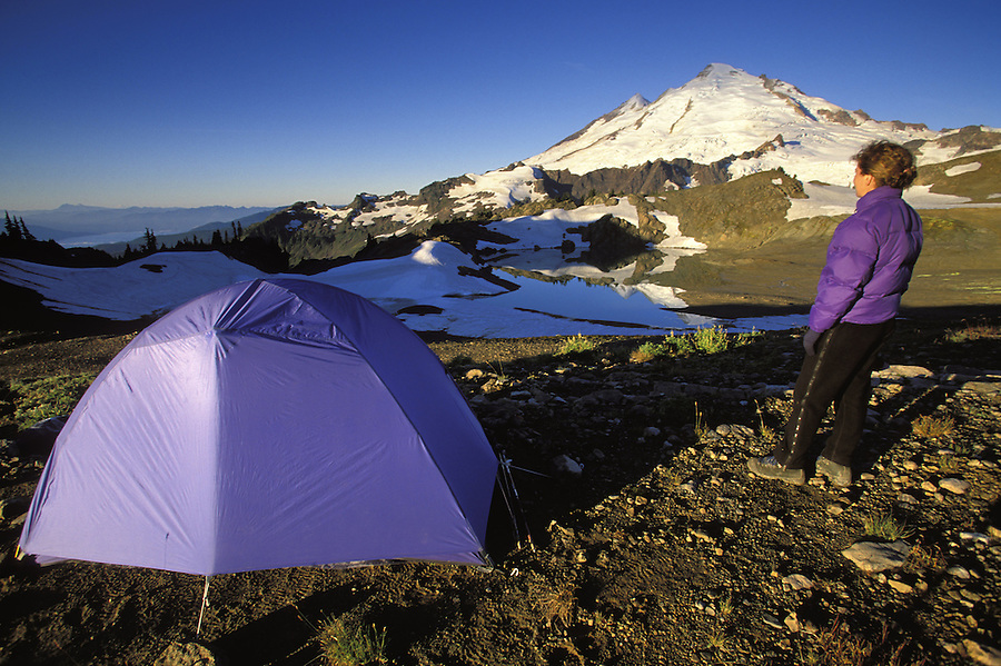 Backpacker beside tent below Mt Baker on a clear morning, North Cascades, Cascade Mountains, Washington