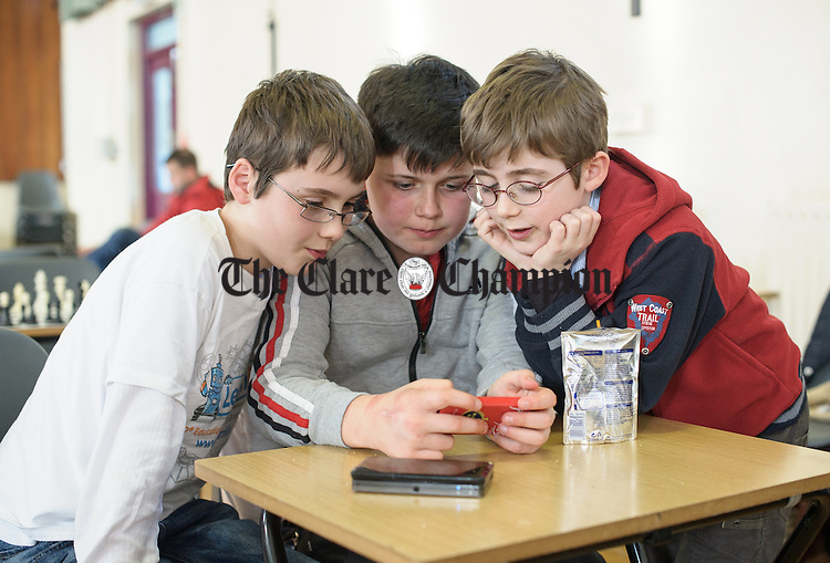 Kilkishen's Tadhg Austin, Colm Kelly of Sixmilebridge and Gearoid Austin of Kilkishen playing with a phone during a break from competition at the Clare Community games chess county finals in St Flannan's college, Ennis. Photograph by John Kelly.