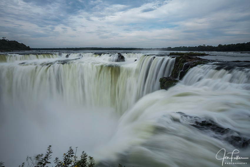 The water of the Iguazu River falls over the precipice of the Garganta del Diablo or the Devil's Throat Waterfall in Iguazu Falls National Park in both Argentina and Brazil.  Both parks are UNESCO World Heritage Sites.  At left is Brazil, at right is Argentina.