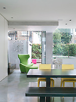 The Grande Papilio swivel chair and foot stool in the kitchen are from B&B Italia, and create another of the bright colours which punctuate the white minimal interior