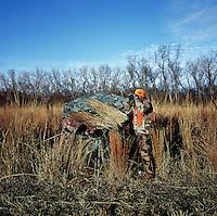 OutdoorLife Editor Andrew McKean (cq) looks for white tail deer through binoculars during a hunt in Superior, Nebraska, Thursday, December 1, 2011. ..Photo by Matt Nager
