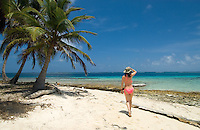 Woman strolls down the  white sand beach of Kuanidup Chico, Comarca De Kuna Yala, San Blas Islands, Panama