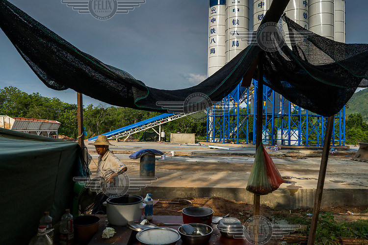 A Chinese migrant stands beside the tent where he sleeps and has his makeshift kitchen at a newly built, Chinese owned, cement plant on the Mekong river where a Chinese company is building a bridge as part of the China-Laos Railway project.