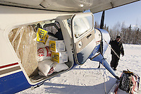 "February 16, 2013  Volunteer Iditarod Air Force pilot,Dave Beckett readies his Helio Courier plane loaded with hay, HEET and musher's food bags bound for Rainy Pass at the Willow airport on the first day of the ""Food Fly"". ..Iditarod 2013    Photo Copyright Jeff Schultz  -- Do not reproduce without written permission"