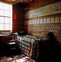The spare bed is covered in ethnic African textiles and the walls in fretwork