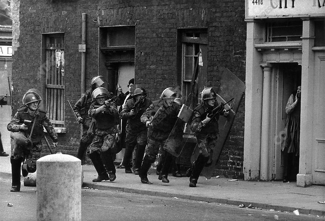English soldiers charge rock throwing youth Londonderry, Northern Ireland, 1970.