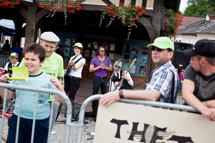 A local band perfrom as they wait see the Tour de France cycling competition pass through their village.