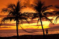 Couple embrace next to palm trees with a hammock, watching a West Maui sunset.