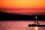 Lake Washington sunset with girl on dock holding rope tied to a small motor boat silhouetted Kirkland Washington State USA