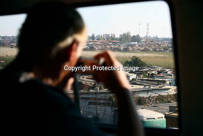 A tourist takes pictures from the tour bus in Chris Hani squatter camp, one of the poorest in Soweto.